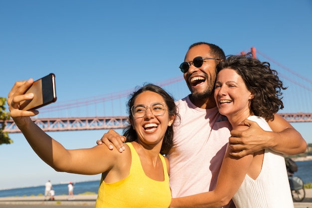 Rozochoceni przyjaciele bierze selfie z smartphone
