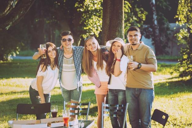Rozochoceni przyjaciele na pinkinie w parku. jedzenie pizzy