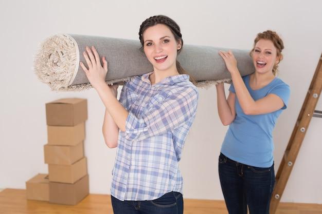 Rozochoceni przyjaciele niesie staczającego się dywanik po ruszać się w domu