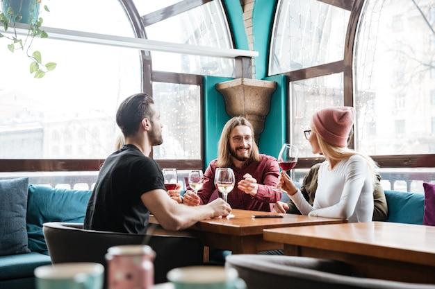 Rozochoceni przyjaciele siedzi w kawiarni i pije alkohol.