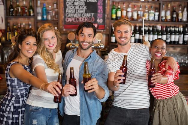 Rozochoceni przyjaciele trzyma piwne butelki przy pubem