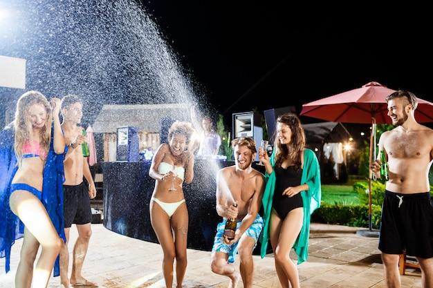 Rozochoceni przyjaciele uśmiecha się, raduje się, odpoczywa przy przyjęciem blisko pływackiego basenu