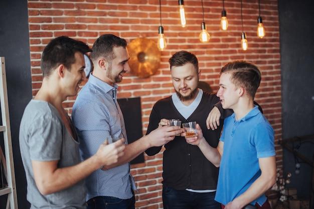 Rozochoceni starzy przyjaciele komunikują między sobą szklanki whisky w pubie. rozrywka i styl życia