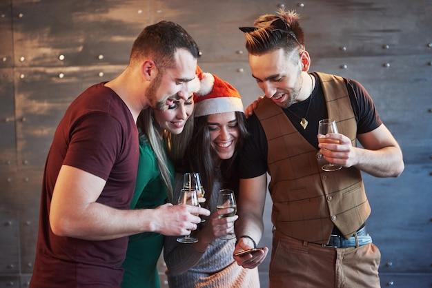 Rozochoceni starzy przyjaciele komunikują się ze sobą i oglądają telefon, kieliszki szampana na przyjęcie noworoczne. pojęcie rozrywki i stylu życia. ludzie połączeni z wi-fi
