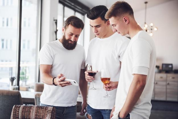 Rozochoceni starzy przyjaciele komunikują się ze sobą i oglądają telefon, kieliszki whisky lub wina w pubie.