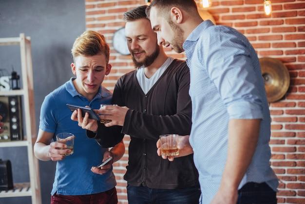 Rozochoceni starzy przyjaciele komunikują się ze sobą i oglądają telefon, kieliszki whisky w pubie. rozrywka styl życia. wi-fi połączonych ludzi na spotkaniu przy stole barowym