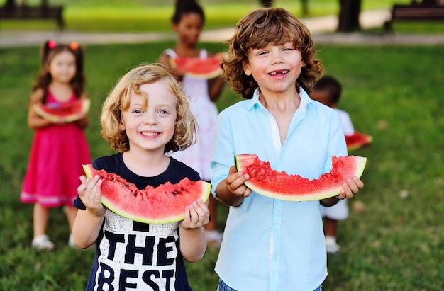 Rozochoceni szczęśliwi dzieci jedzą dojrzałego arbuza w parku na trawie w pogodnym letnim dniu