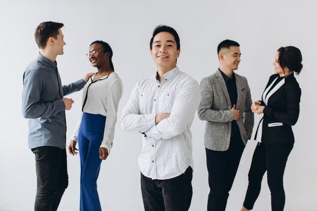 Rozochoceni wielorasowi profesjonalni ludzie biznesu śmia się wpólnie stojący w rzędzie blisko ściany, szczęśliwa różnorodna młoda grupa pracowników, grupa pracowników korporacyjnych, zabawa, koncepcja zasobów ludzkich