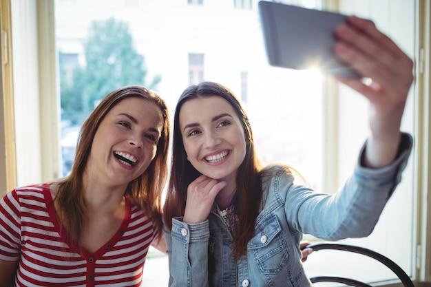 Rozochoceni żeńscy przyjaciele bierze selfie przy sklep z kawą