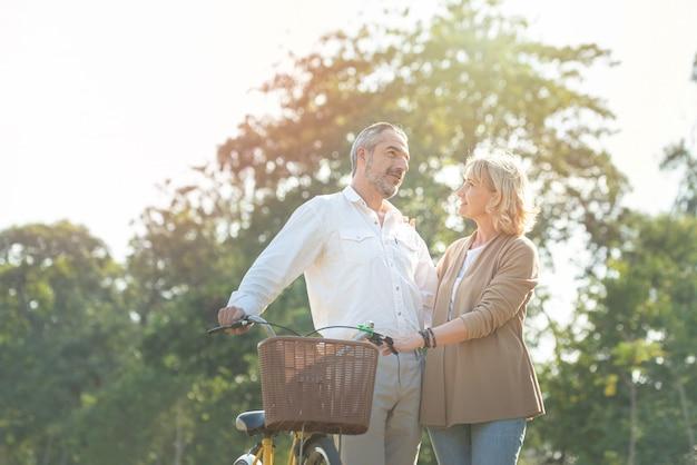 Rozochocona aktywna starsza para z rowerowym odprowadzeniem przez parka wpólnie. idealne zajęcia dla osób starszych w wieku emerytalnym.