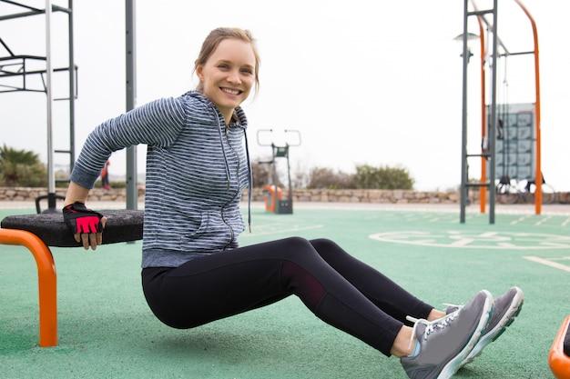 Rozochocona atleta dziewczyna trenuje ręki i klatki piersiowej mięśnie