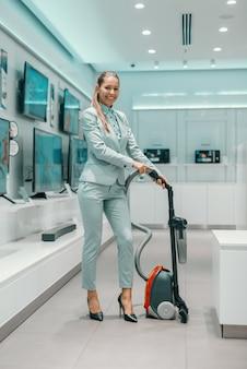 Rozochocona atrakcyjna brunetka w formalnej odzieży pozuje z nowym odkurzaczem w technika sklepie
