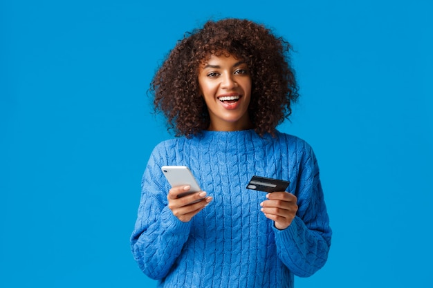Rozochocona atrakcyjna uśmiechnięta afroamerykańska kobieta kupuje online, robi zakupy podczas rabata sezonu wakacyjnego, ono uśmiecha się, trzyma smartphone i kredytową kartę stoi trwanie błękit