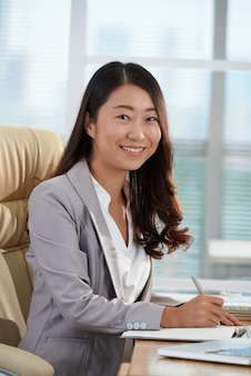 Rozochocona azjatycka biznesowa kobieta pozuje przy biurkiem w biurze