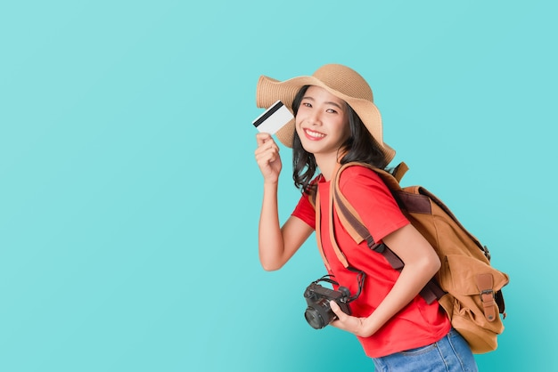 Rozochocona azjatycka kobieta trzyma kredytową kartę przygotowywającą podróżować