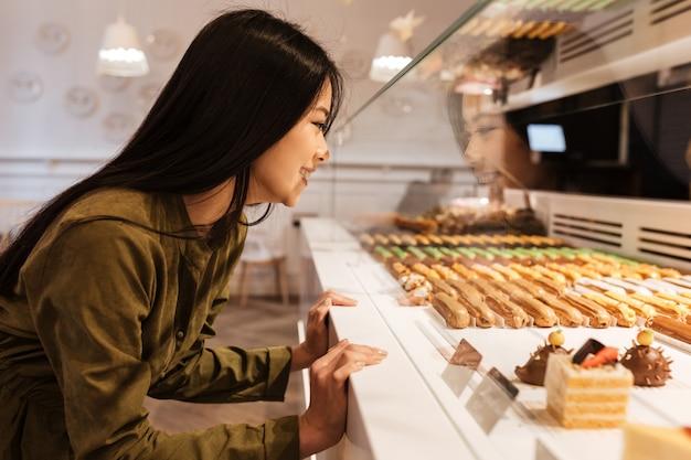 Rozochocona azjatykcia młoda dama patrzeje sweeties.