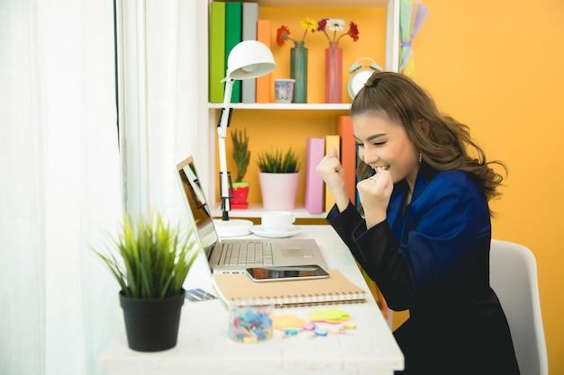 Rozochocona biznesowa dama pracuje na laptopie w biurze