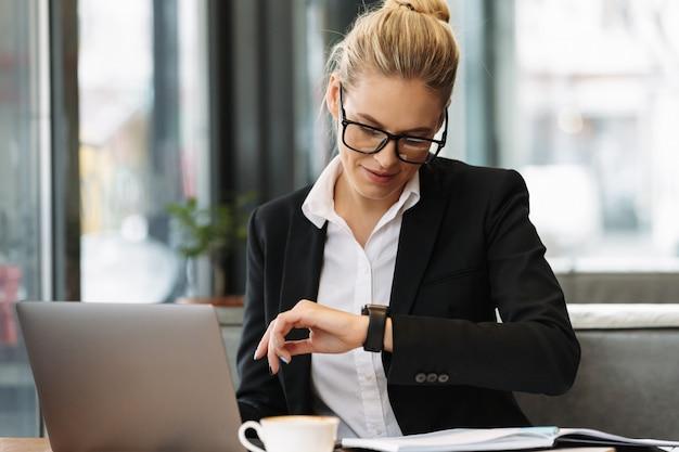 Rozochocona biznesowa kobieta patrzeje zegarek.