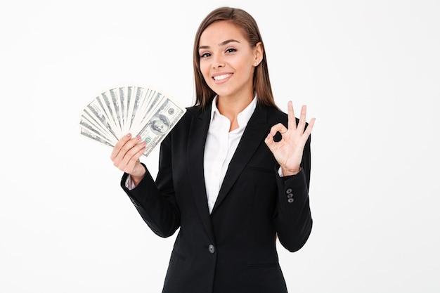 Rozochocona biznesowa kobieta pokazuje zadowalającego gesta mienia pieniądze
