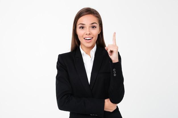 Rozochocona biznesowa kobieta wskazuje copyspace.