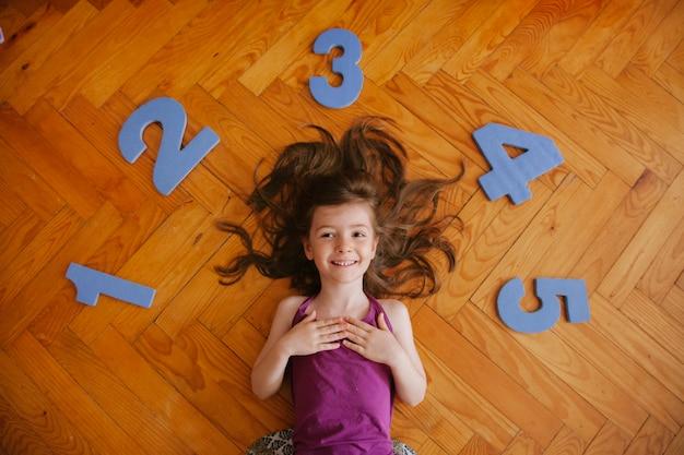 Rozochocona blondynki dziewczyna bawić się z liczbami w domu