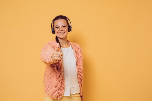 Rozochocona brunetka w szkłach i hełmofonach ubierał w różowego puloweru białej bluzce i kolorze żółtym dyszy szeroki ono uśmiecha się, wskazujący przy kamerą nad żółtym tłem z kopii przestrzenią. pozytywny i młody.