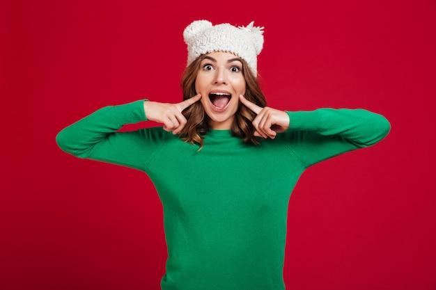 Rozochocona brunetki kobieta w pulowerze i śmiesznym kapeluszu