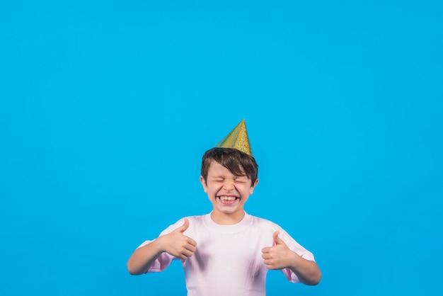 Rozochocona chłopiec gestykuluje thumbup przeciw plamy tłu