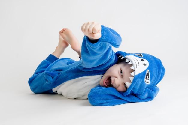 Rozochocona chłopiec pozuje na białym tle w piżamie, błękitnego rekinu kostium