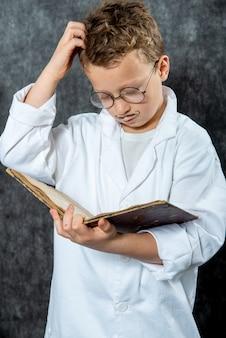 Rozochocona chłopiec retro z białej bluzki czytelniczą książką
