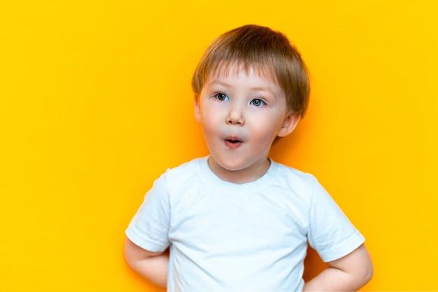 Rozochocona chłopiec trzy lat w białych koszulka stojakach