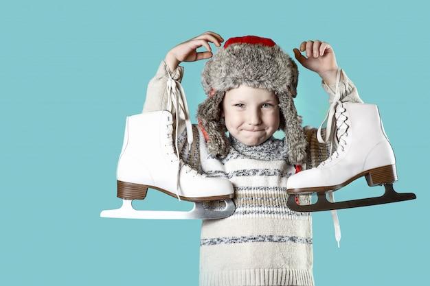 Rozochocona chłopiec trzyma lodowe łyżwy na błękitnym tle w kapeluszu z nausznikami