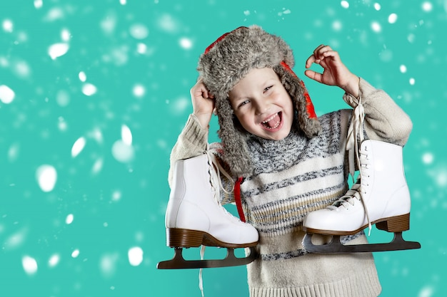 Rozochocona chłopiec trzyma lodowe łyżwy w kapeluszu z nausznikami