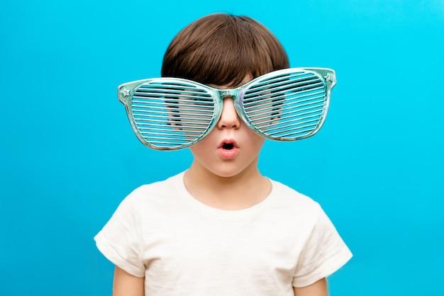 Rozochocona chłopiec w dużych szkłach wyraża zdziwioną twarz odizolowywającą na błękit ścianie