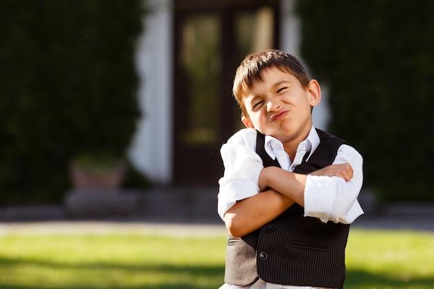 Rozochocona chłopiec w modnym kostiumu na zielonej trawie