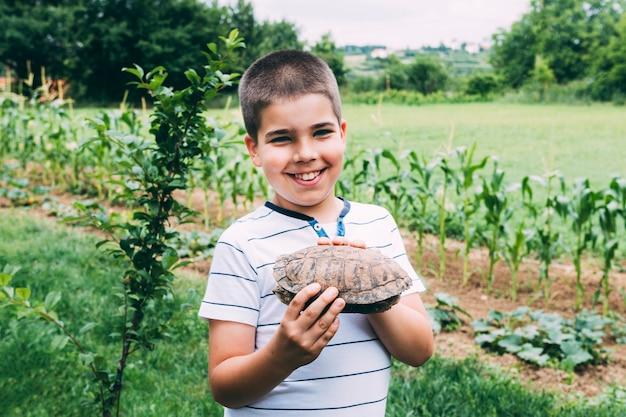 Rozochocona chłopiec z żółwiem w ogródzie