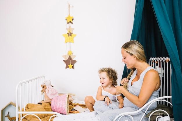 Rozochocona ciężarna matka i dziecko na łóżku
