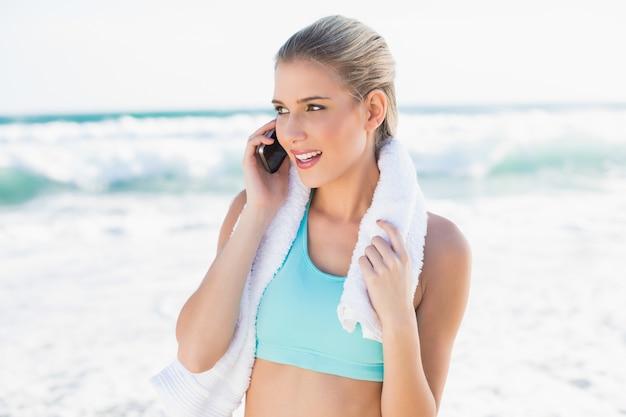 Rozochocona dysponowana blondynka w sportswear na telefonie