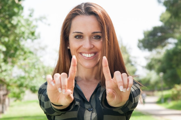 Rozochocona dziewczyna pokazuje palce wskazujących przy kamerą