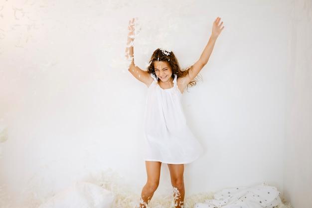 Rozochocona dziewczyna skacze pod spada piórkami