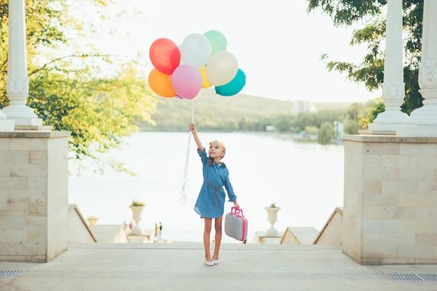 Rozochocona dziewczyna trzyma kolorowych balony i dziecięcą walizkę