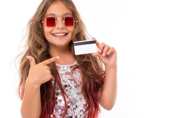 Rozochocona dziewczyna trzyma plastikową bank kartę i wskazuje przy nim w kwadratowych czerwonych okularach przeciwsłonecznych odizolowywających