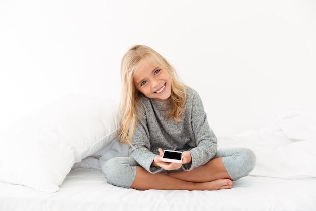 Rozochocona Dziewczyna Trzyma Smartphone W Szarych Piżamach Podczas Gdy Siedzący Na łóżku Darmowe Zdjęcia