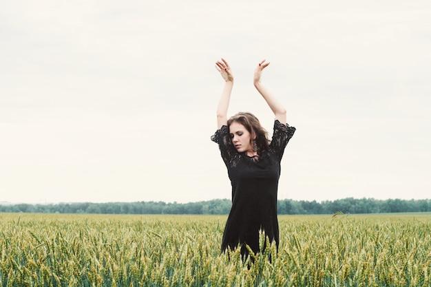 Rozochocona dziewczyna w czarnej koronkowej sukni tanczy samotnie w zielonym pszenicznym polu