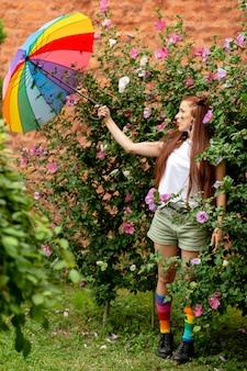 Rozochocona dziewczyna z lgbt tęczą na jej twarzy i kolorowym parasolem pozuje przy naturą