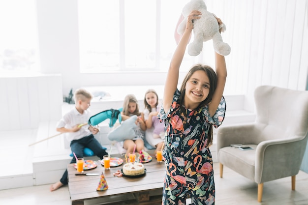 Rozochocona dziewczyna z zabawkarskim królikiem na przyjęciu urodzinowym