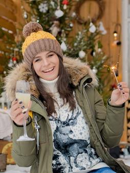 Rozochocona dziewczyny kapeluszu puszka kurtka z sparklers z szklanym szampanem w jej ręce świętuje