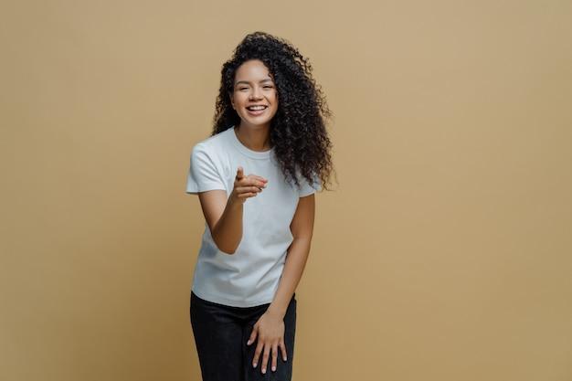 Rozochocona energiczna młoda kobieta z kędzierzawym afro włosy wskazuje palec wskazujący naprzód