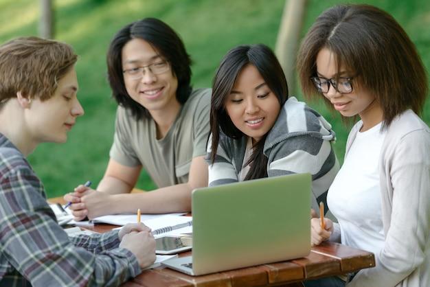 Rozochocona grupa młodzi ucznie siedzi i studiuje