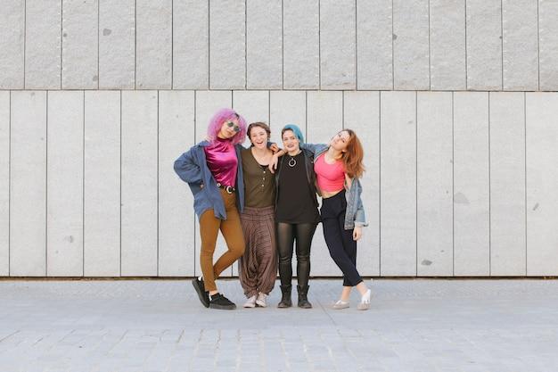Rozochocona grupa nastoletnie kobiety ściska ich przyjaźń i pokazuje